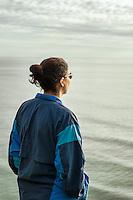 Solitary adult woman appreciates the ocean surise.