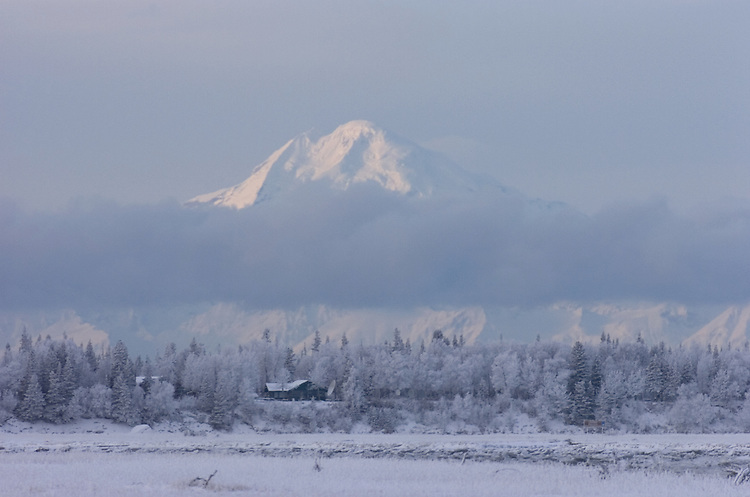 Mount Redoubt rises above a bank of ice fog hanging above the Kenai River near its mouth in downtown Kenai, Alaska. The 10,197-foot active volcano is the dominant landmark on the horizon of the southcentral Alaskan community.