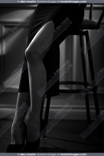 Black and white closeup of sexy legs of a woman wearing a tight black skirt with a long high cut sitting on a bar stool in a dimly lit room