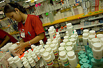 ALGODONES, MEXICO-MARCH 23: An saleswoman at Guadalahara Pharmacy restocks shelves March 23, 2005 in Algodones. Medications sold are often one third to one half less expensive than in the U.S.   ©Radhika Chalasani