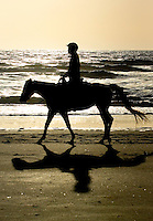 A woman silhouetted rides a horse along the beach in Amelia Island, FL