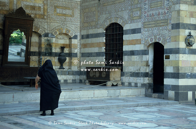 Woman in a black burqa outside the Azm Palace, Damascus, Syria.