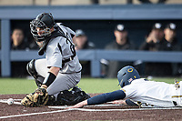 Western Michigan Broncos catcher Jesse Forestell (27) reaches for Michigan Wolverines baserunner Miles Lewis (3) as he slides into home on March 18, 2019 in the NCAA baseball game at Ray Fisher Stadium in Ann Arbor, Michigan. Michigan defeated Western Michigan 12-5. (Andrew Woolley/Four Seam Images)