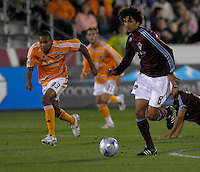 Colorado midfielder Mehdi Ballouchy pushes the ball up the field ahead of Ricardo Clark (13, orange). The Houston Dynamo defeated the Colorado Rapids 3-1 at Dick's Sporting Goods Park, Denver, Colorado. Saturday, October 4, 2008. Photo by Trent Davol/isiphotos.com.