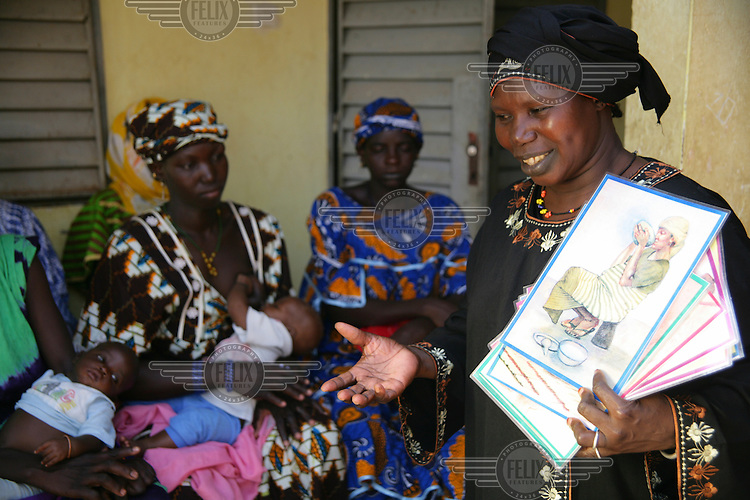 A health worker giving a talk about breastfeeding and the importance of good nutrition at a mother and baby clinic.