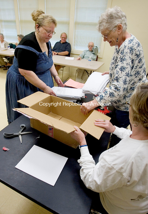WOODBURY CT. 02 June 2013-060313SV11-From left, Anne Cushman Schwaikert , Democratic Registrar of Voters , and Judith Henderson, Republican Registrar of Voters unpack ballots for recount in Woodbury Monday. Election officials held a hand recount of the 634 ballots cast in Thursday's town budget referendum. The machine vote resulted in a 317-317 tie.<br /> Steven Valenti Republican-American