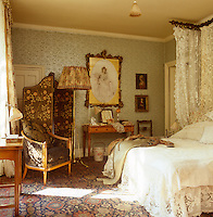 A delicately patterned Victorian bedroom, its silvery-blue wallpaper glistening in the warm light from the window