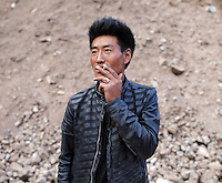 A young Tibetan man smokes by the side of a road in the Amdo region of the Tibetan Plateau.  Up to 100,000 nomads have been removed from the highland grasslands of the Tibetan Plateau. Climate change, mining and government policy are causing the rapid disappearance of this unique culture.