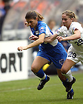 Mia Hamm tries to beat Leslie Gaston (29) to the ball at RFK Stadium in Washington, DC on 4/26/03 during a game between the Atlanta Beat and Washington Freedom