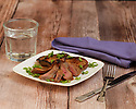 Pork chop grilled and sliced, served on a white plate with chopped green onion