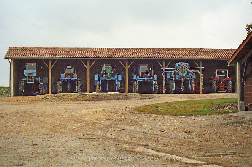 Winery building. Mechanical harvesting tractor. Chateau la Tour de By, Medoc, Bordeaux, France
