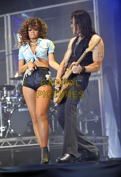 Rihanna (Robyn Rihanna Fenty).Rihanna performs at Day Two V Festival at Hylands Park, Chelmsford, Essex, England..August 21st, 2011.stage concert live gig performance music full length denim knotted shirt belly stomach midriff micro shorts black pearls brooch fishnet stockings guitar funny ankle boots.CAP/ROS.©Steve Ross/Capital Pictures