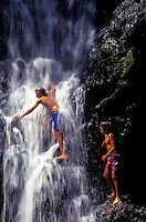Kids jump off rocks by a gorgeous cascading waterfall on the Big Island of Hawaii.