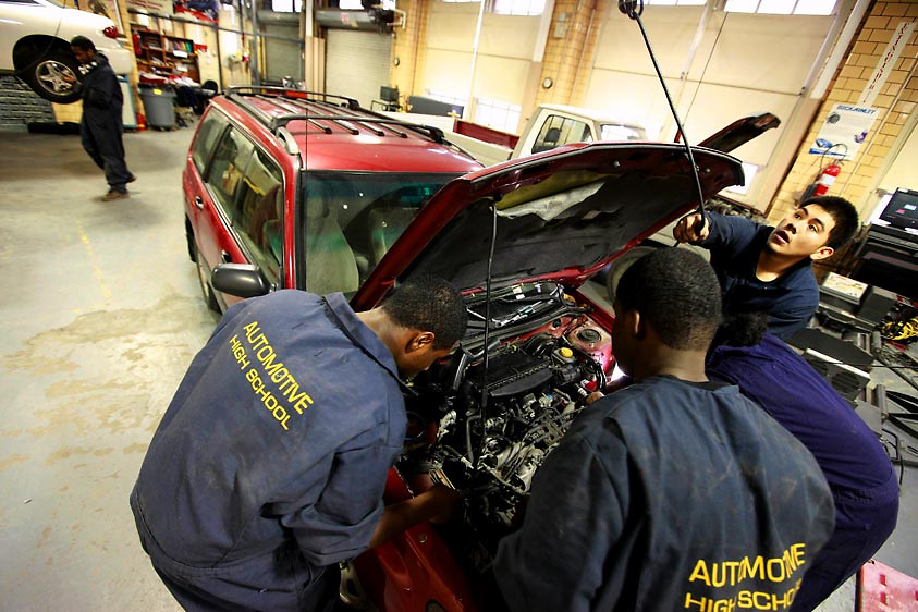 Automotive HS, Brooklyn, NY on Friday, January 22, 2010.  High school students have the opportunity to participate in a special program where they perform basic maintenance and repairs on privately owned cars at very competitive prices.  (r. to l. ):  Students David Genis, 17; Dwayne Cadet, 18; Harry Cange, 17; and Joshua Smalls, 17, perform a tune-up on a car.