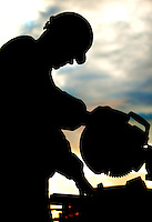 Silhouetted worker running a miter saw.