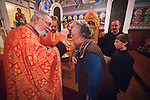 Rev. Stephen Tumbas anoints the forehead of parishioner Ilene Votaw  forehead with oil at the conclusion of the Christmas Eve Vigil Service, St. Sava Serbian Orthodox Church, Jackson, Calif.