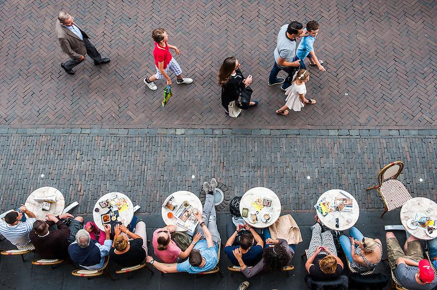 Nederland, Utrecht, 28 juni 2014<br /> Stadsbeeld, binnenstad van Utrecht, centrum. Mensen wandelen voor het terras van Grand cafe de Winkel van Sinkel langs. Tafeltjes op het trottoir. <br /> Foto (c) Michiel Wijnbergh