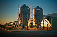 Grain elevator at egg farm bathed in sunset light on a cold winter day.