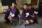 Boys school children in classroom at Wangdue Chhoeling Lower Secondary School, Bumthang, Bhutan..Bhutan the country that prides itself on the development of 'Gross National Happiness' rather than GNP. This attitude pervades education, government, proclamations by royalty and politicians alike, and in the daily life of Bhutanese people. Strong adherence and respect for a royal family and Buddhism, mean the people generally follow what they are told and taught. There are of course contradictions between the modern and tradional world more often seen in urban rather than rural contexts. Phallic images of huge penises adorn the traditional homes, surrounded by animal spirits; Gross National Penis. Slow development, and fending off the modern world, television only introduced ten years ago, the lack of intrusive tourism, as tourists need to pay a daily minimum entry of $250, ecotourism for the rich, leaves a relatively unworldly populace, but with very high literacy, good health service and payments to peasants to not kill wild animals, or misuse forest, enables sustainable development and protects the country's natural heritage. Whilst various hydro-electric schemes, cash crops including apples, pull in import revenue, and Bhutan is helped with aid from the international community. Its population is only a meagre 700,000. Indian and Nepalese workers carry out the menial road and construction work.