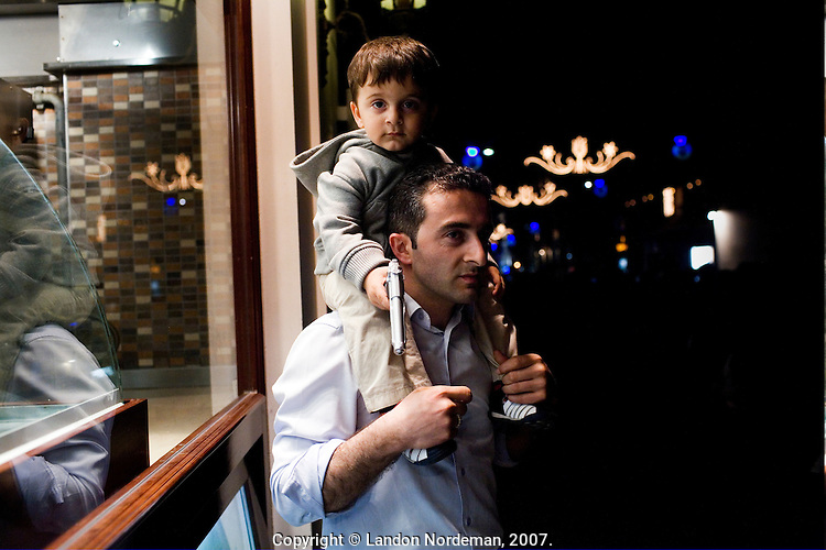 ISTANBUL - MAY 26, 2007:   A boy with his toy gun, sits atop his father's shoulders in stanbul, Turkey. Photo by Landon Nordeman.