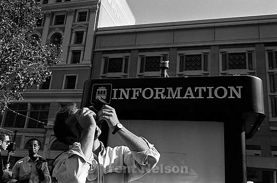 Photographer and &quot;information&quot; sign. Leica hip shots on the street.<br />