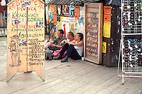 Friends age 24 sitting on ground chilling out in outdoor market.  Zakopane Poland