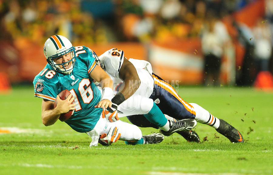 Nov. 18, 2010;  Miami, FL, USA; Miami Dolphins quarterback (16) Tyler Thigpen is sacked by Chicago Bears defensive end (69) Henry Melton in the first quarter at Sun Life Stadium. Mandatory Credit: Mark J. Rebilas-