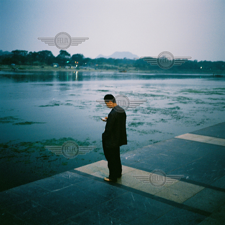 A man checks his mobile phone on the riverside in Guilin.