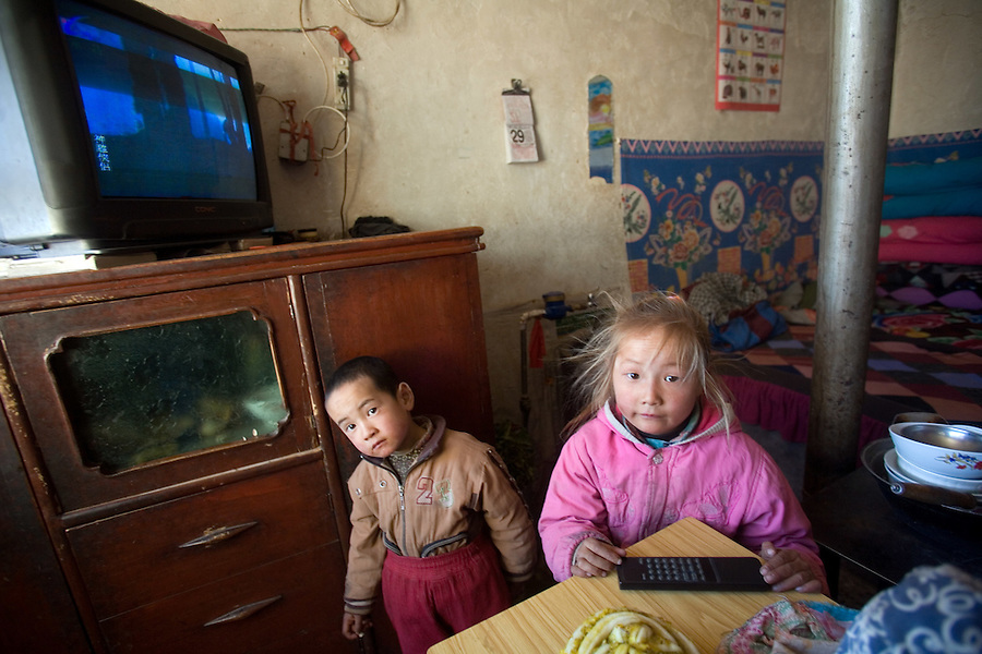 Blonde-haired Gu Meina, 6 (R),  with her brother in her modest home near Liqian Village.