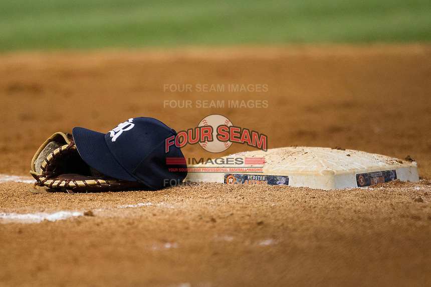 Rice Owls baseball hat and glove sitting by first base in-between innings of the NCAA baseball game against the TCU Horned Frogs on March 1, 2014 during the Houston College Classic at Minute Maid Park in Houston, Texas. Rice defeated TCU 1-0. (Andrew Woolley/Four Seam Images)