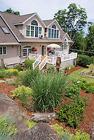 House and home landscaping backyard with raised deck, ornamental grasses, mulched beds, slope hill, shrubs, trees, sunny open yard, roof windows, rocks