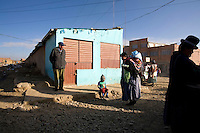 A woman carries a baby on her back on a street in El Alto.
