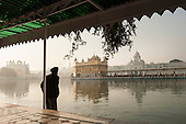 Amritsar, Punjab, India.  The Golden Temple - Harmandir Sahib - at dawn with an old Sikh bathing his feet in the holy waters.