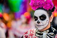 A young woman, dressed as La Catrina, a Mexican pop culture icon representing the Death, walks through the town during the Day of the Dead procession in Mexico City, Mexico, 29 October 2016. Day of the Dead (Día de Muertos), a syncretic religious holiday combining the death veneration rituals of the ancient Aztec culture with the Catholic practice, is celebrated throughout all Mexico. Based on the belief that the souls of the departed may come back to this world on that day, people gather at the gravesites in cemeteries praying, drinking and playing music, to joyfully remember friends or family members who have died and to support their souls on the spiritual journey.