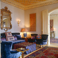 Brightly coloured Turkish rugs and soft indigo coloured seating set the tone for this opulently furnished downstairs sitting room