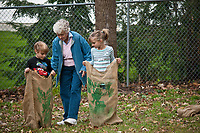 Janice Mosher helps her grandchildren, Codi, left, and Kayla Mosher run a burlap bag race at the annual Ned Mosher Apple Butter Festival. The festival held at the Knox-Metzker log cabin on the grounds of McVay Elementary School in Westerville every year helps raise money to maintain the cabin as a teaching tool for students at the school.