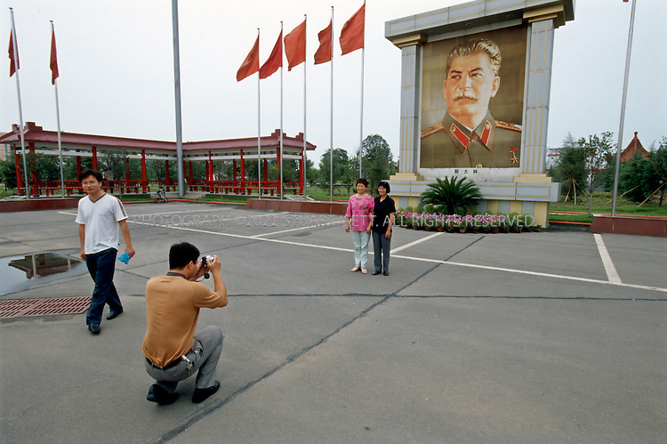 "7/15/2005--Nanjie Village, Henan Province, China..Tourists visiting Nanjie village, a model communist village in the central province of Henan, pose in front of an image of Stalin in the village's main square. Nanjie collectivised its agricultural production and industry in the mid 1980s - when the rest of the country was doing the opposite, introducing market reforms put forward by former leader Deng Xiaoping. Although the teachings of the ""Great Helmsman"" serve as the moral compass for the 3,100 people of Nanjie, the real secret to its collective well-being is, well, capitalist: two dozen village enterprises manufacturing all sorts of things ? noodles, beer, pharmaceuticals. One even promotes ""red tourism.""..It continues to be run on Maoist egalitarian lines and has become something of a tourist attraction because of its staunch adherence to the values of the past. .Photograph By Stuart Isett.All photographs ©2005 Stuart Isett.All rights reserved."