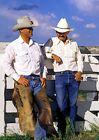 Two cowboys in traditional western attire of chaps and ten gallon hats pose under a big sky near a corral on a ranch. Colorado.
