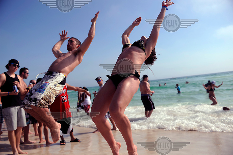 Students doing backflips during Spring Break on Panama city beach in Florida.