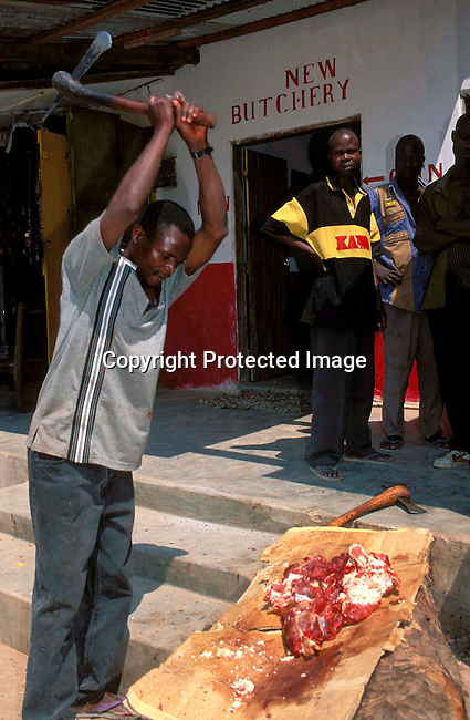 dirobros00041 Malawi, Zomba..A man using an ax to chop meat, probably beef, outside of a local butchery.  Several bystanders watch as the meat is chopped on a large tree trunk..Commerce, trade, business, market, food sales..©Robert J. Ross/iAfrika Photos