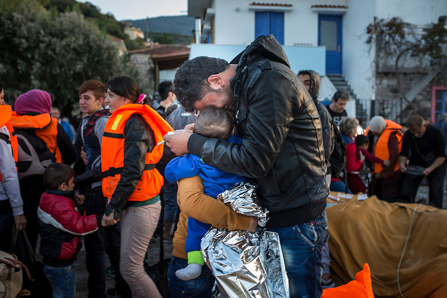 A man hugs his wife and child and cries after being rescued and brought to the island of Lesbos, Greece, when the rubber dingy they were traveling in from Turkey had mechanical problems.
