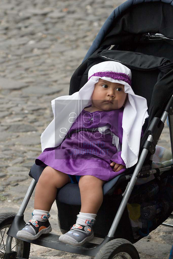 A baby dressed as a cucurucho during the Penance of Jesus procession.