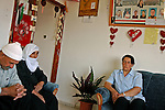 Amal Mahmoud, right, a security prisoner released on parole, with her parents at home in the Druze village of Majdal Shams, Golan Heights. Amal was convicted for attempt to smuggle weapons from Syria to Palestinian militant groups. Pictures of her fellow prisoners are hung on the wall.