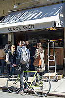 Customers wait outside for their Montreal style bagels at the Black Seed bagelry in Nolita  in New York on Thursday, April 24, 2014.  The hand rolled  bagels are boiled in honey water and baked in a wood-burning oven. (© Frances M. Roberts)