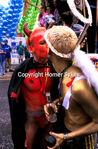 'GAYFEST MANCHESTER, UK', DRESSED AS A DEVIL AND AN ANGEL TWO MEN KISS EACH OTHER DURING THE PARADE, THROUGH MANCHESTER,