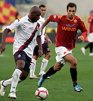 Calcio, Serie A: Roma vs Bologna. Roma, stadio Olimpico, 1 novembre 2009..Football, Italian serie A: Roma vs Bologna. Rome, Olympic stadium, 1 november 2009. AS Roma forward Mirko Vucinic, of Montenegro, right, challenges  Bologna midfielder Gaby Mudingayi, of Belgium..UPDATE IMAGES PRESS/Riccardo De Luca