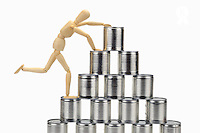 Wooden mannequin climbing tin cans pyramid (Licence this image exclusively with Getty: http://www.gettyimages.com/detail/102918622 )