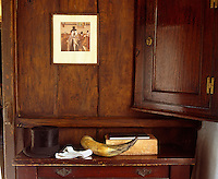 A bowler hat and other objects on top of a 17th-century court cupboard, a forerunner of the Welsh dresser