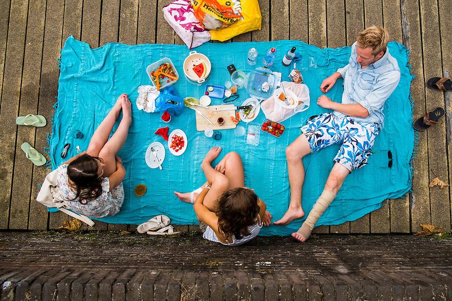 Nederland, Utrecht, 20 juli  2014<br /> Jongelui, studenten picknicken op een kleedje in het centrum van Utrecht aan het water.  <br /> Foto (c) Michiel Wijnbergh