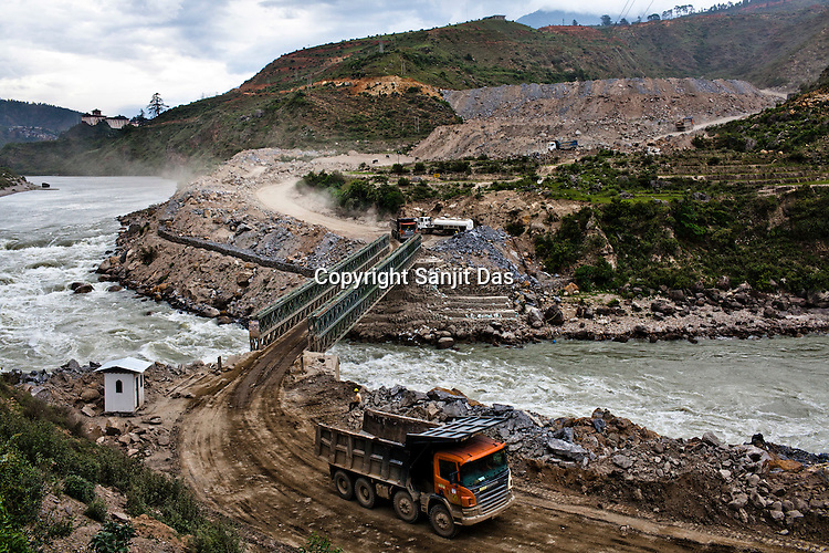 Trucks carry construction material over the Punatsangchu river at the Punatsangchu Hydro Power Project site in Punakha, Bhutan. Photo: Sanjit Das/Panos
